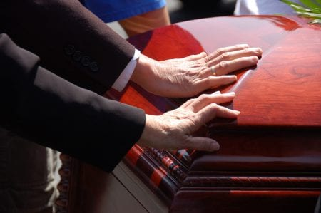 Hands On Casket At A Funeral Stock Photo
