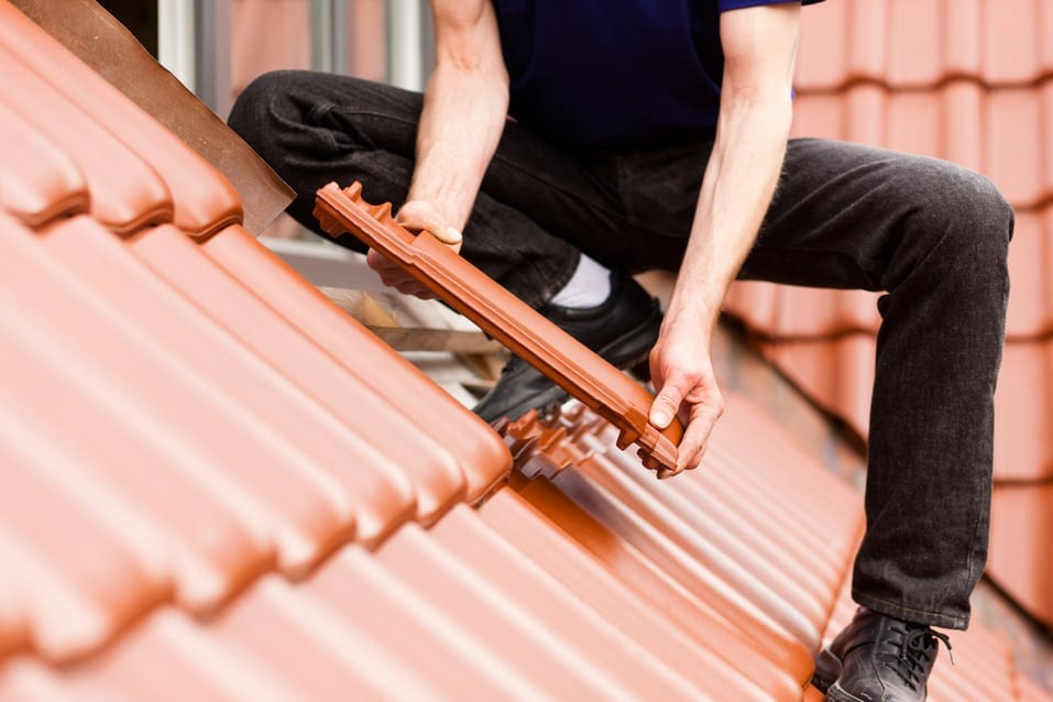 Male Worker Replacing Shingles On A Roof Stock Photo