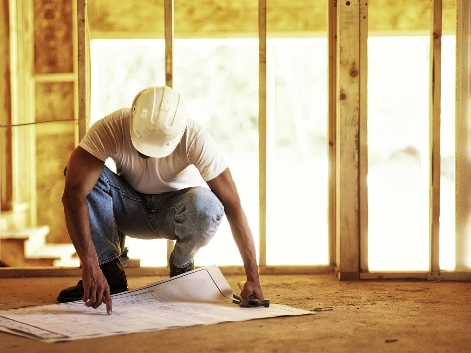 Construction Worker Reviewing Blueprints Stock Photo