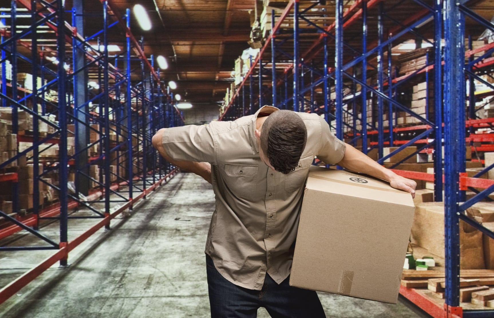 Warehouse Worker Experiencing Lower Back Pain Stock Photo