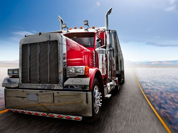 Red 18-wheeler Truck Driving On A Rural Highway Stock Photo