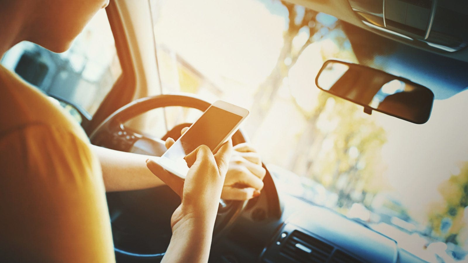 Young Woman Texting While Driving Stock Photo
