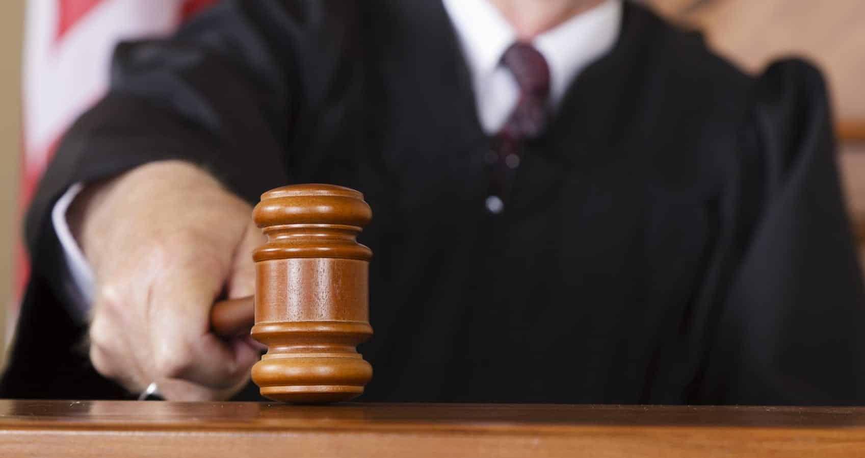 Judge Slamming Gavel Inside Courtroom Stock Photo