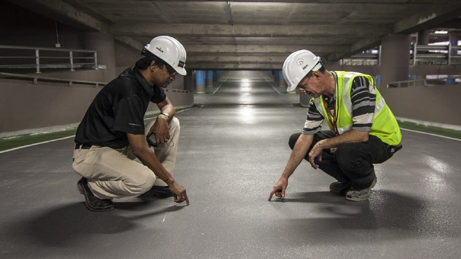 Construction Workers Examining The Road In A Garage Stock Photo