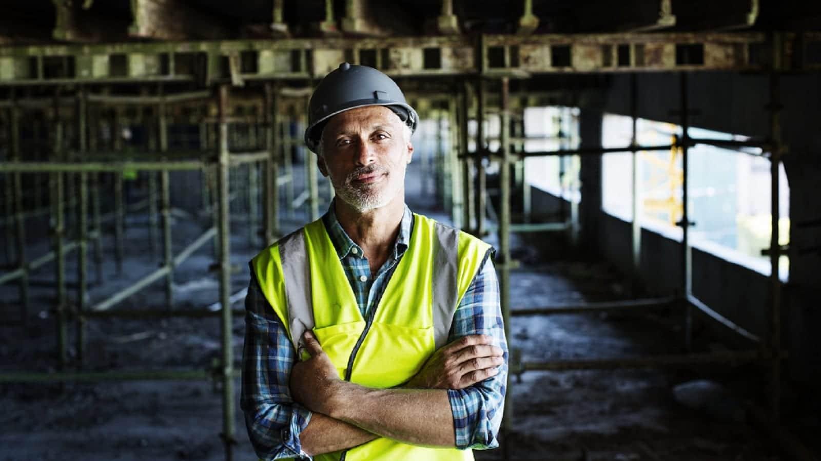 Construction Worker Standing Near Scaffolding Stock Photo