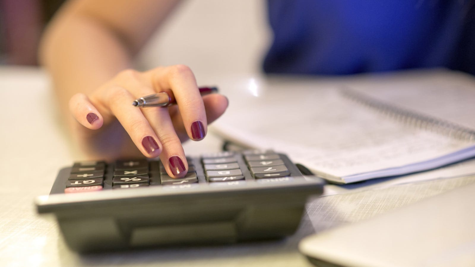 Woman Using Calculator At Desk Stock Photo