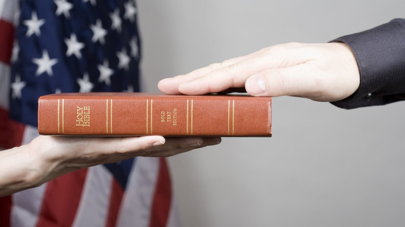 Man Placing Hand On The Bible Inside A Courtroom Stock Photo