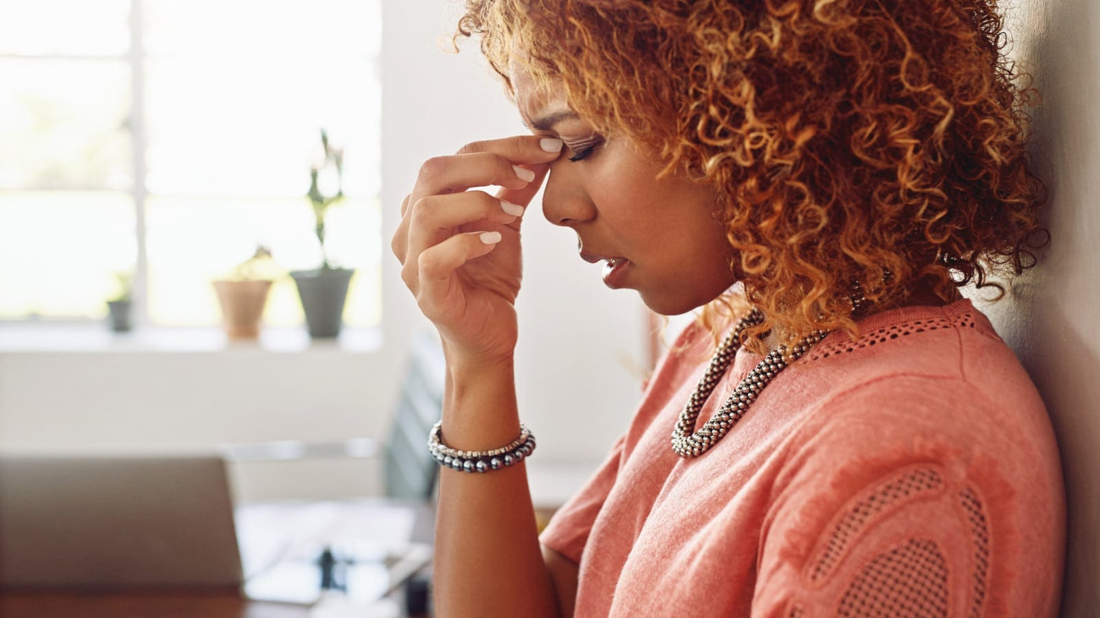 Woman Experiencing A Headache At Work Stock Photo
