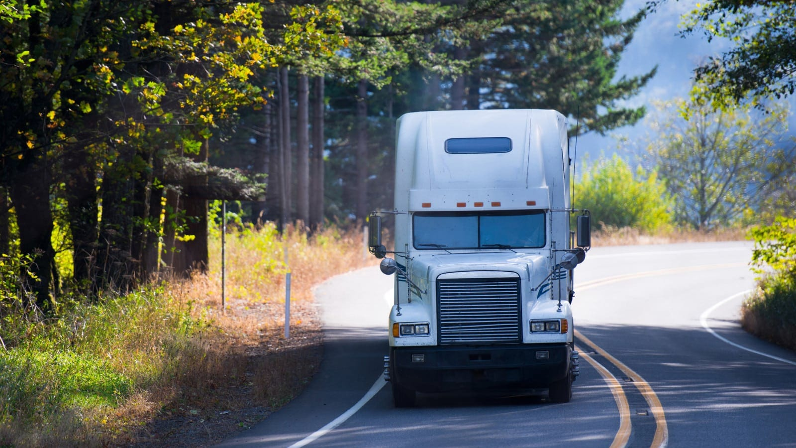White Semi-truck Driving On A Rural Road Stock Photo