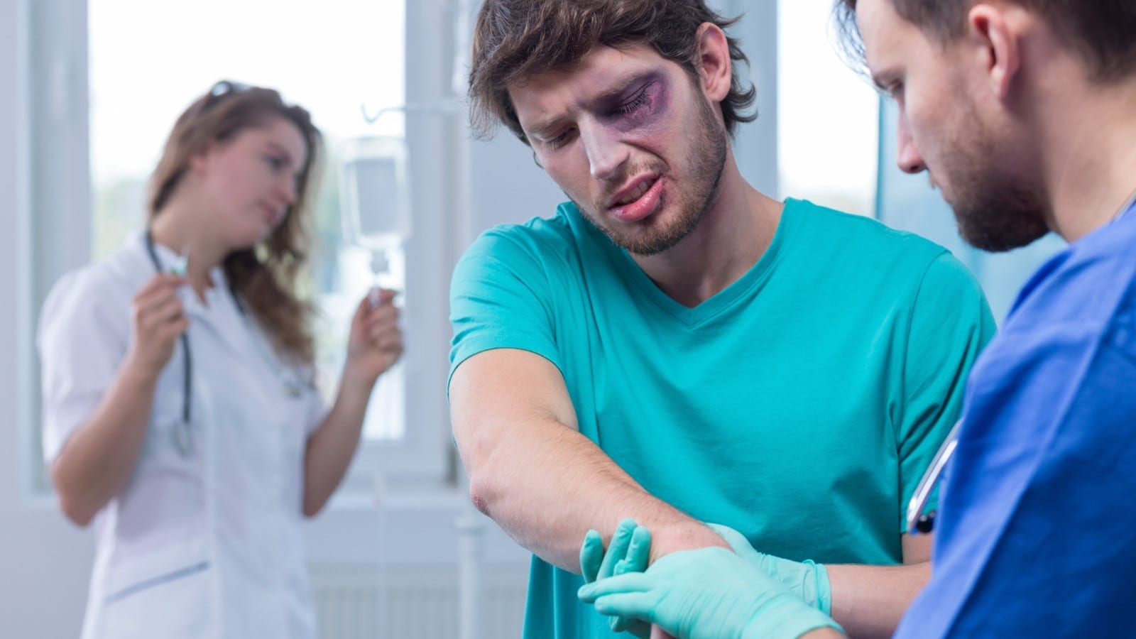 Man With Injured Eye And Arm Being Examined By Nurse