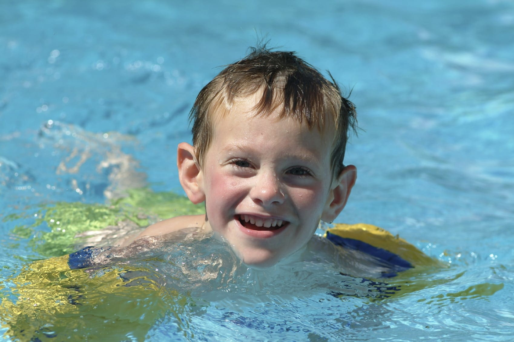 Young Boy Swimming In A Backyard Pool Stock Photo