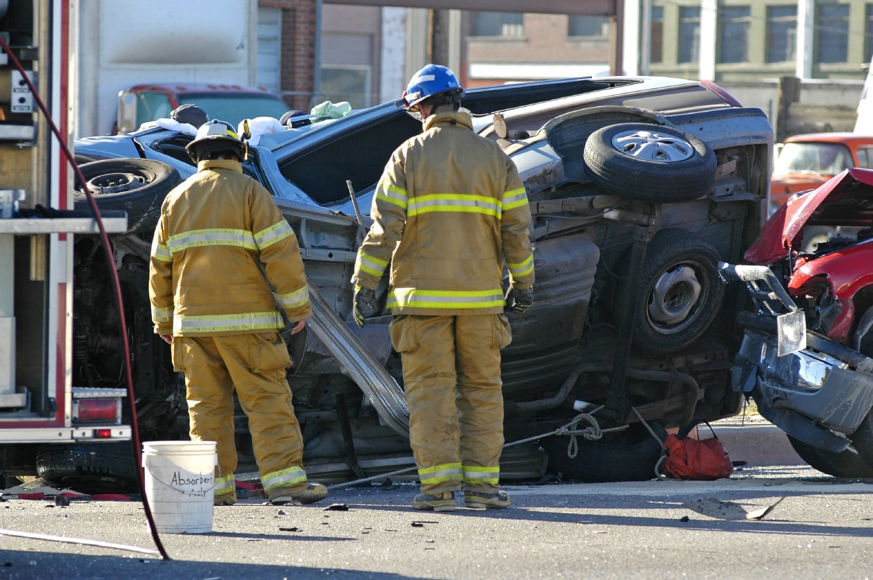 Firefighters Examining Rollover Car Accident Stock Photo