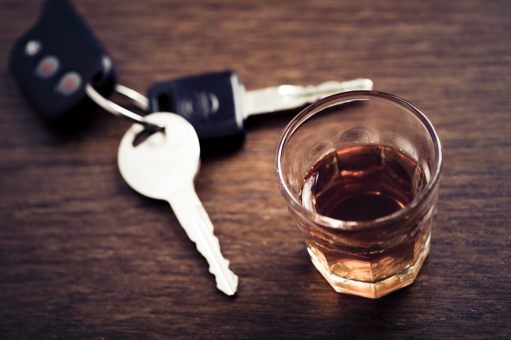 Car Keys Laying Next To A Glass Of Alcohol Stock Photo