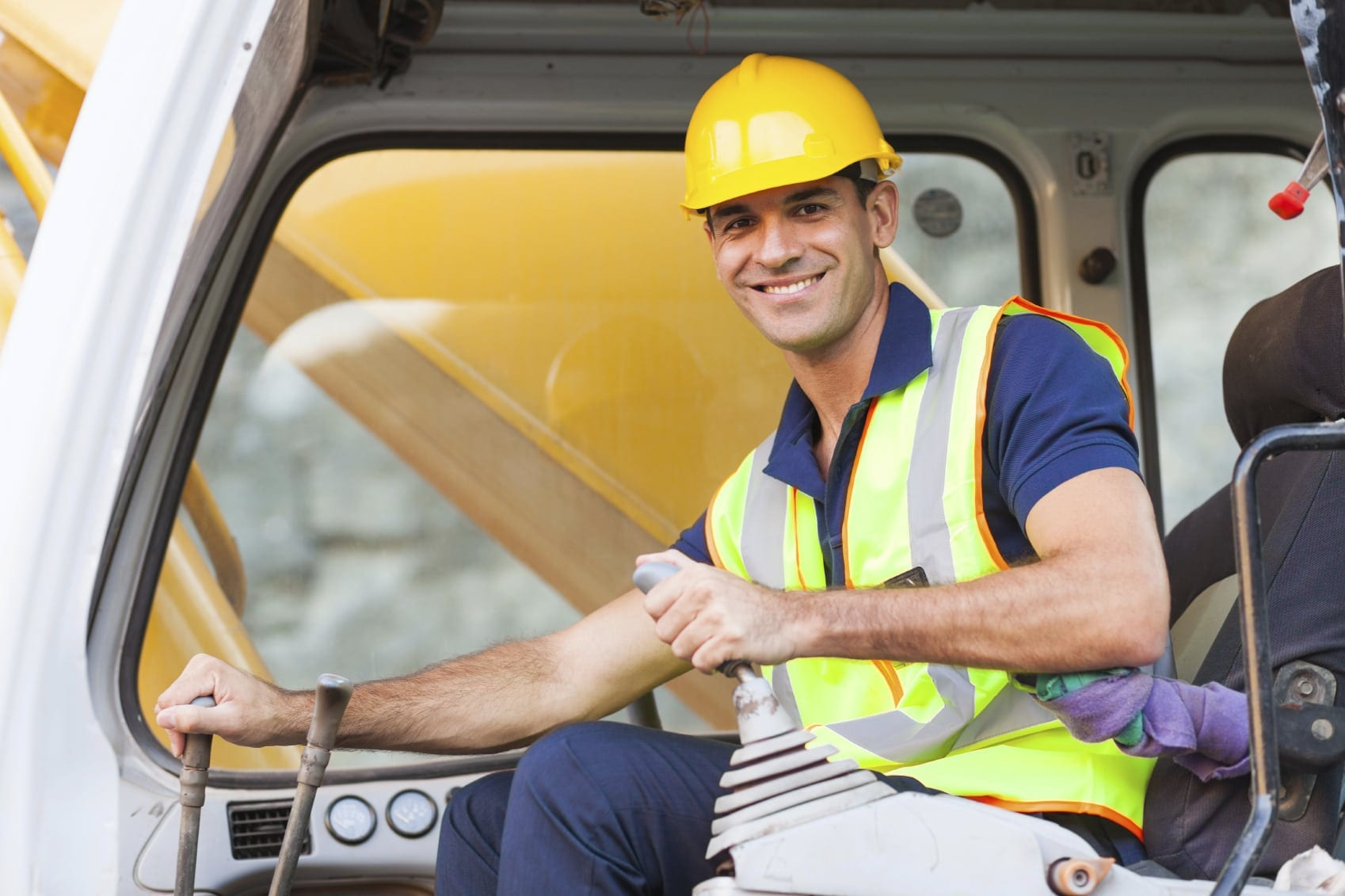 Worker In Hard Hat Driving A Dump Truck Stock Photo