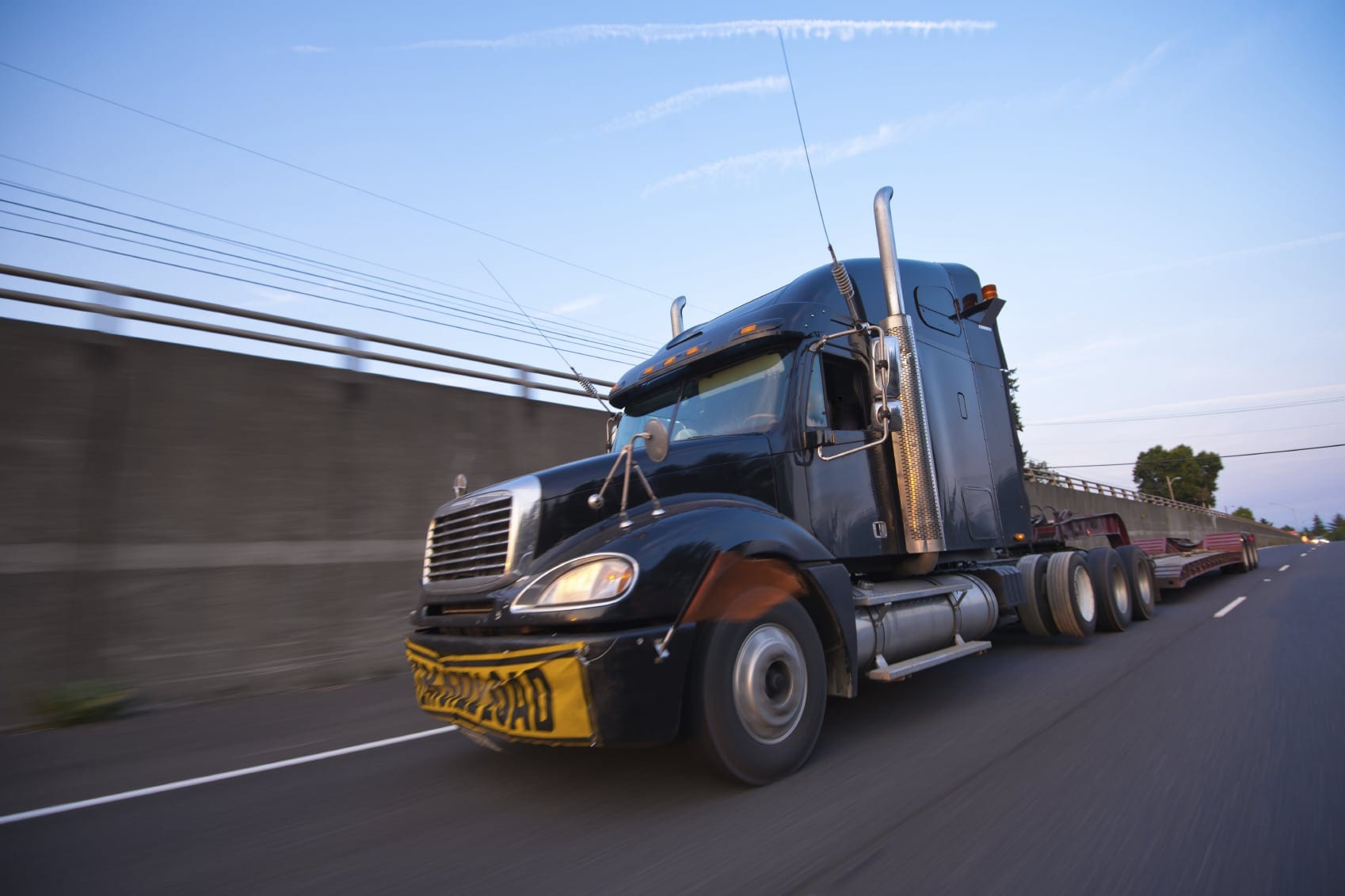 Black Semi-truck Driving On An Interstate Stock Photo
