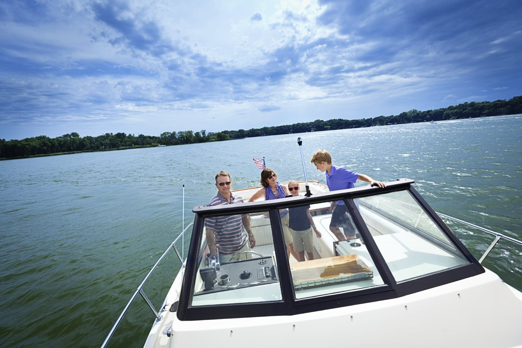 Family Riding A Boat On A Lake Stock Photo
