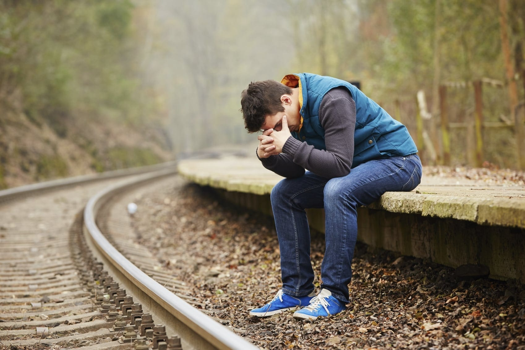 Grieving Young Man Sitting Outdoors Stock Photo
