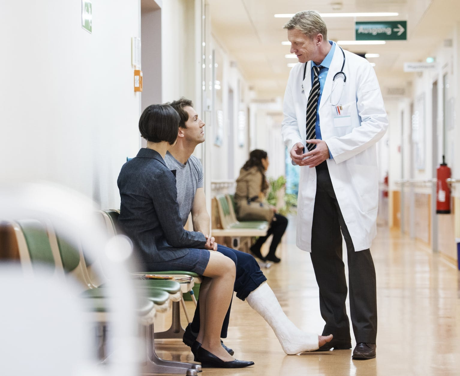 Physician Speaking With Injured Man And Wife Stock Photo