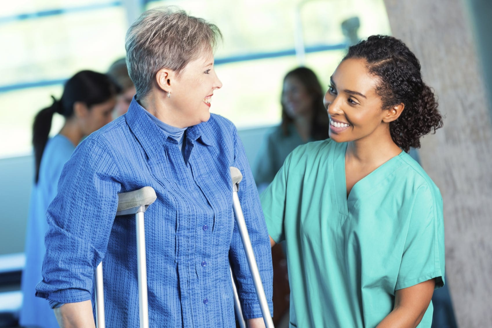 Young Nurse Helping Injured Woman On Crutches Stock Photo