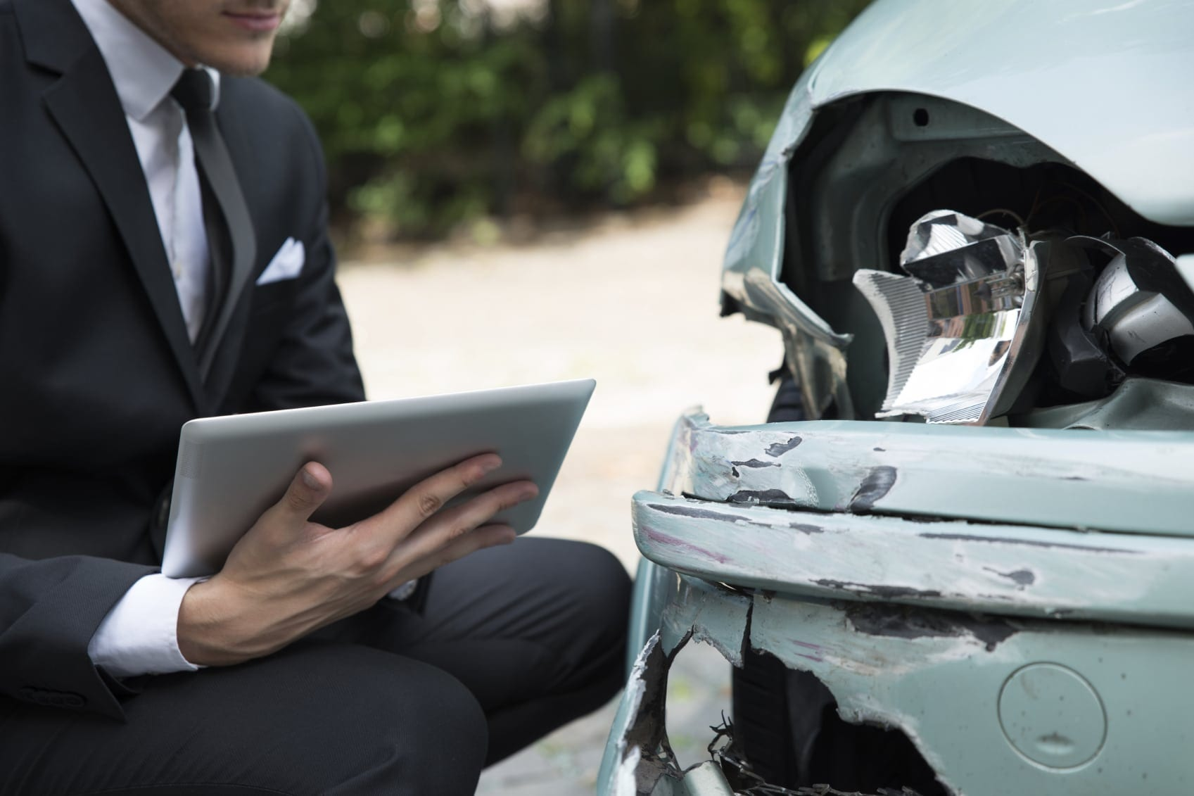 Insurance Adjuster Examining Damaged Car After An Accident