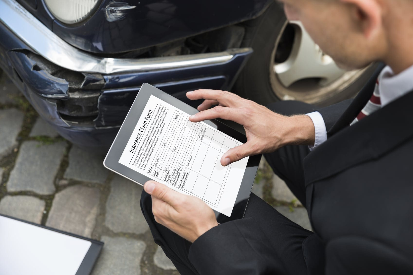 Insurance Adjuster Examining Car After Car Accident Stock Photo