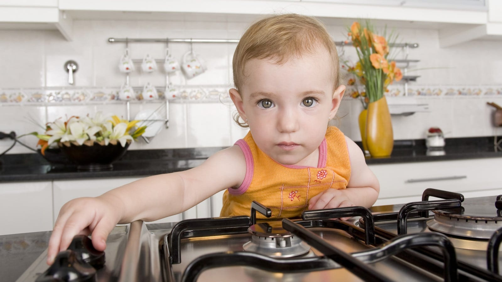 Baby Playing With Switches On Stove Stock Photo