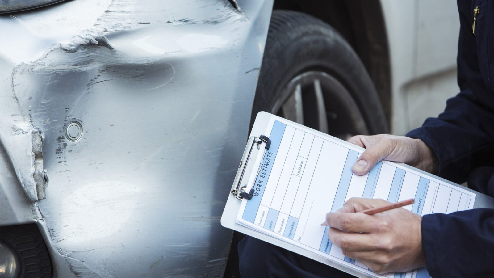 Insurance Adjuster Examining Damage To A Vehicle Stock Photo