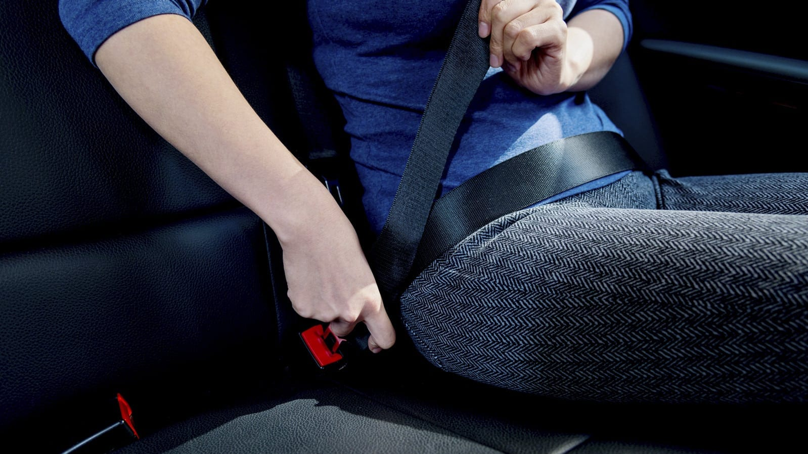 Woman Fastening Seat Belt Inside Car Stock Photo
