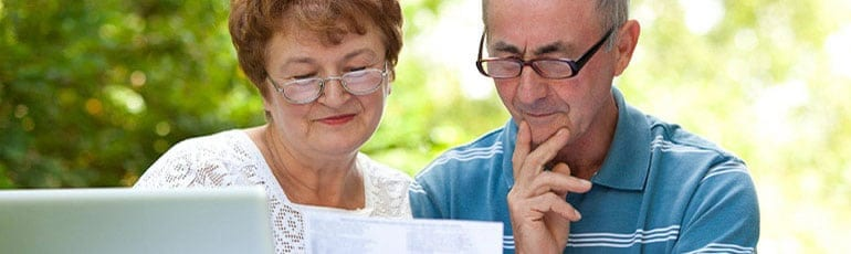 Elderly Couple Reviewing Medical Forms Stock Photo
