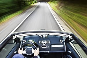 Convertible Driving On Rural Road Stock Photo