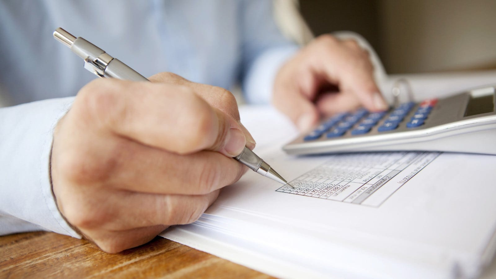 Male Using A Calculator At His Desk Stock Photo