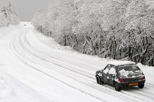 Small Car Driving On A Snowy Road Stock Photo
