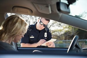 Police Officer Writing A Ticket For A Female Driver Stock Photo