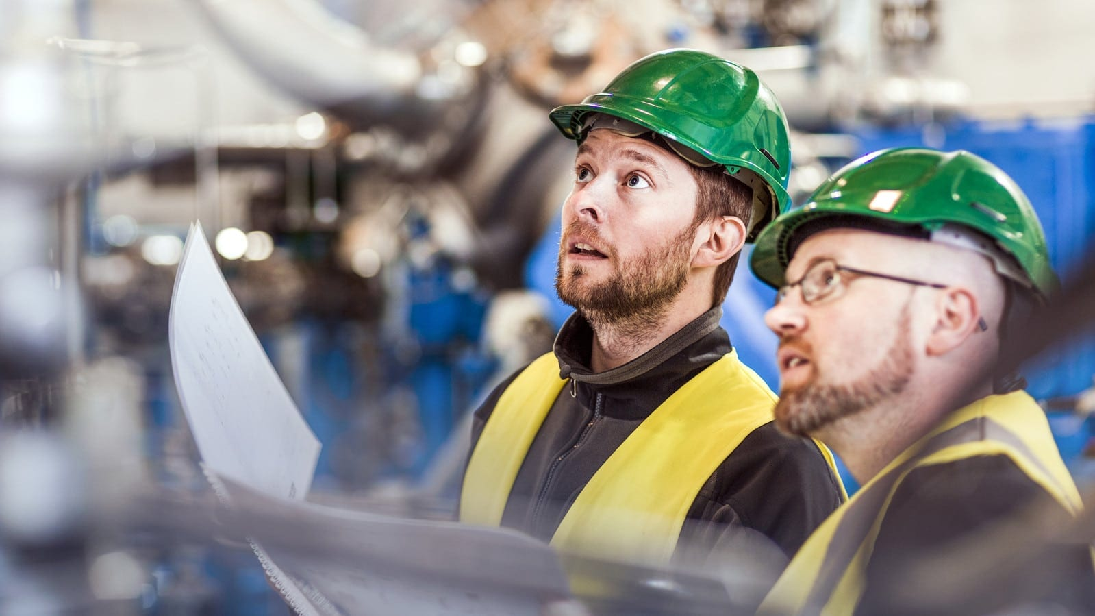 Two Factory Workers In Green Hard Hats Stock Photo