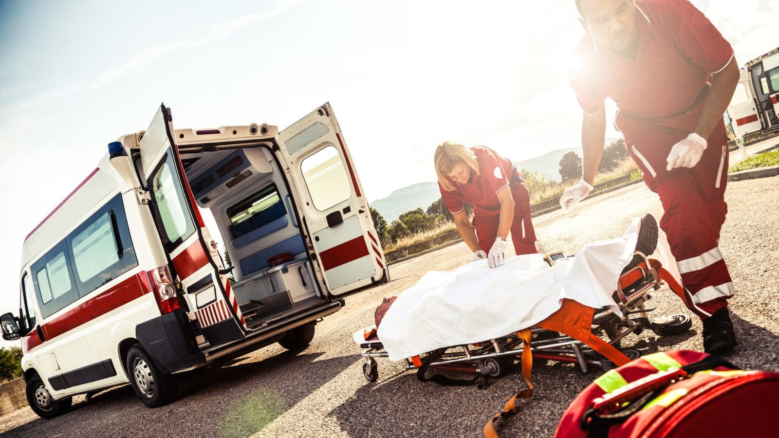 Paramedics Loading An Injured Man Onto A Stretcher Stock Photo