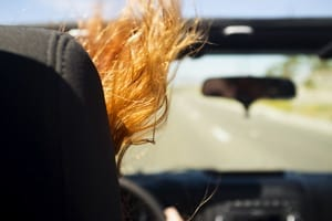 Female Driving A Convertible In High Wind Stock Photo