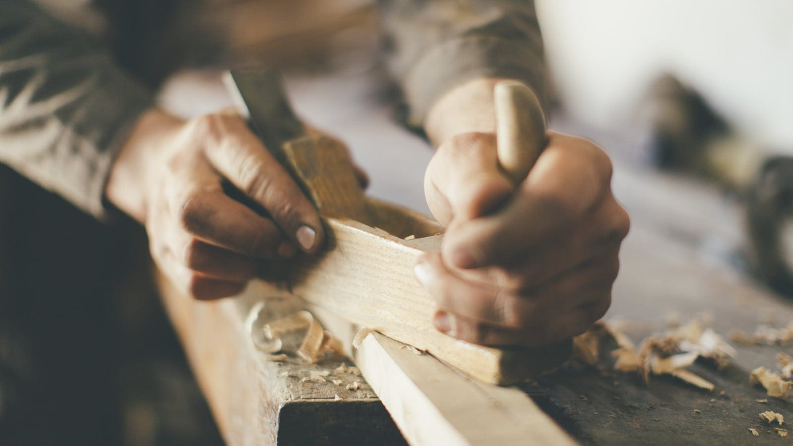 Man Carving Wood Inside A Shop Stock Photo