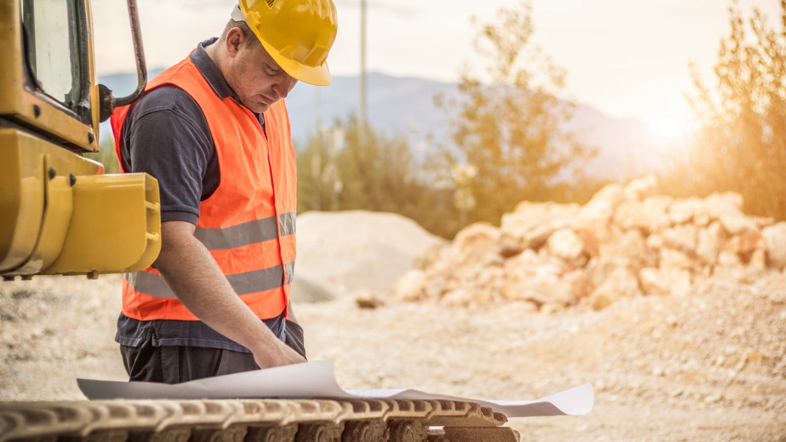 Construction Worker Examining Blueprints On A Job Site Stock Photo