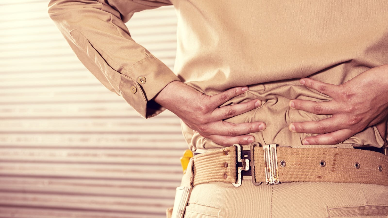 Blue Collar Worker Clutching Lower Back Stock Photo