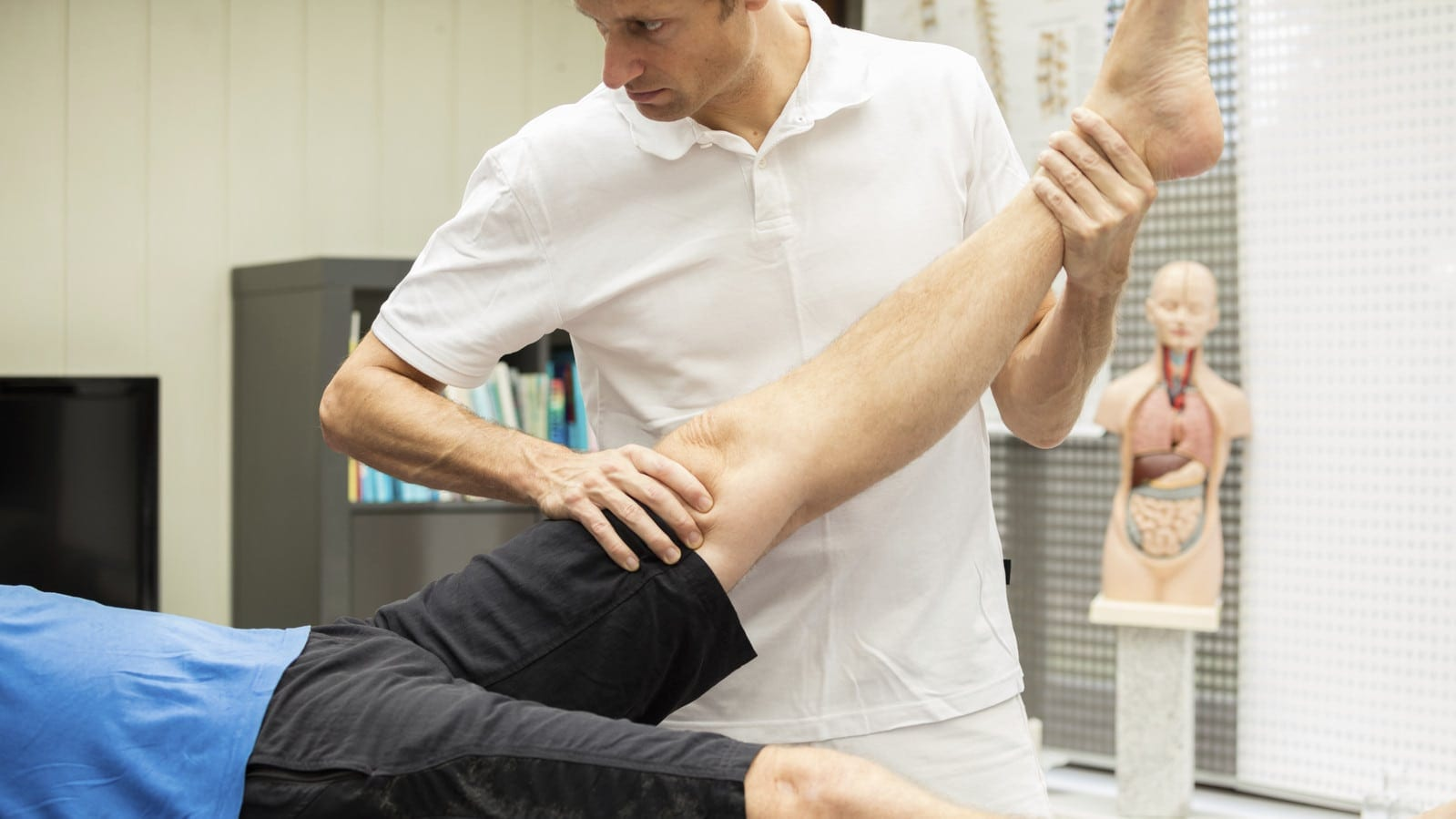 Medical Professional Examining Man's Injured Leg Stock Photo