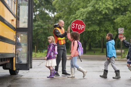 Happy crossing guard gives children high fives as they board school bus