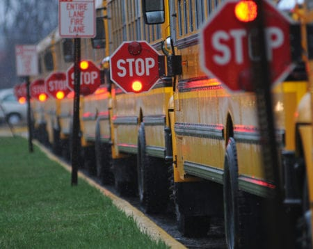 Line of school buses with Stop signs flashing.