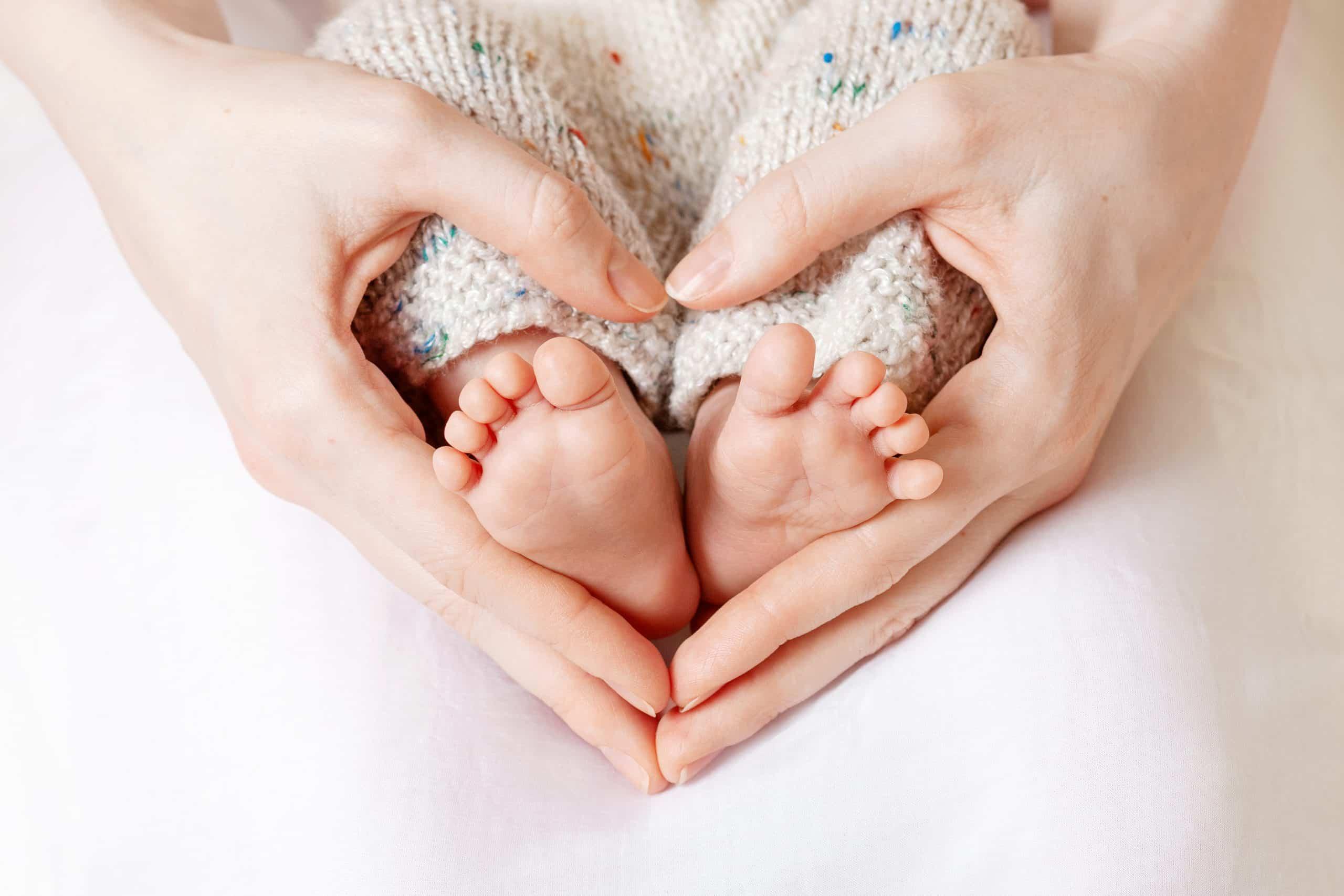 a mother cradling her newborn baby's feet