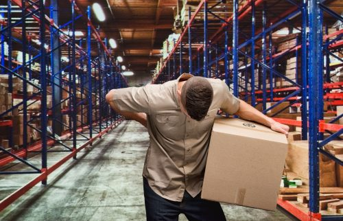 A man working in a warehouse holding his back in pain while carrying boxes.